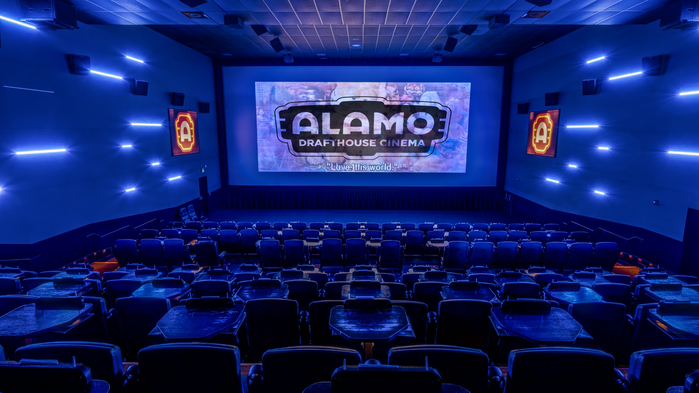 A dark theater with the Alamo Drafthouse logo projected on-screen, ready to start the show.